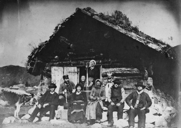 Svarthvittbilde som viser menn og kvinner sittende foran tømmerbygning med gress på taket.