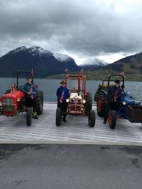 Tre eldre traktorar pynta med bjørkeris og norske flagg, og menn med fine hattar og flagg. Fjord og fjelllandskap i bakgrunnen.