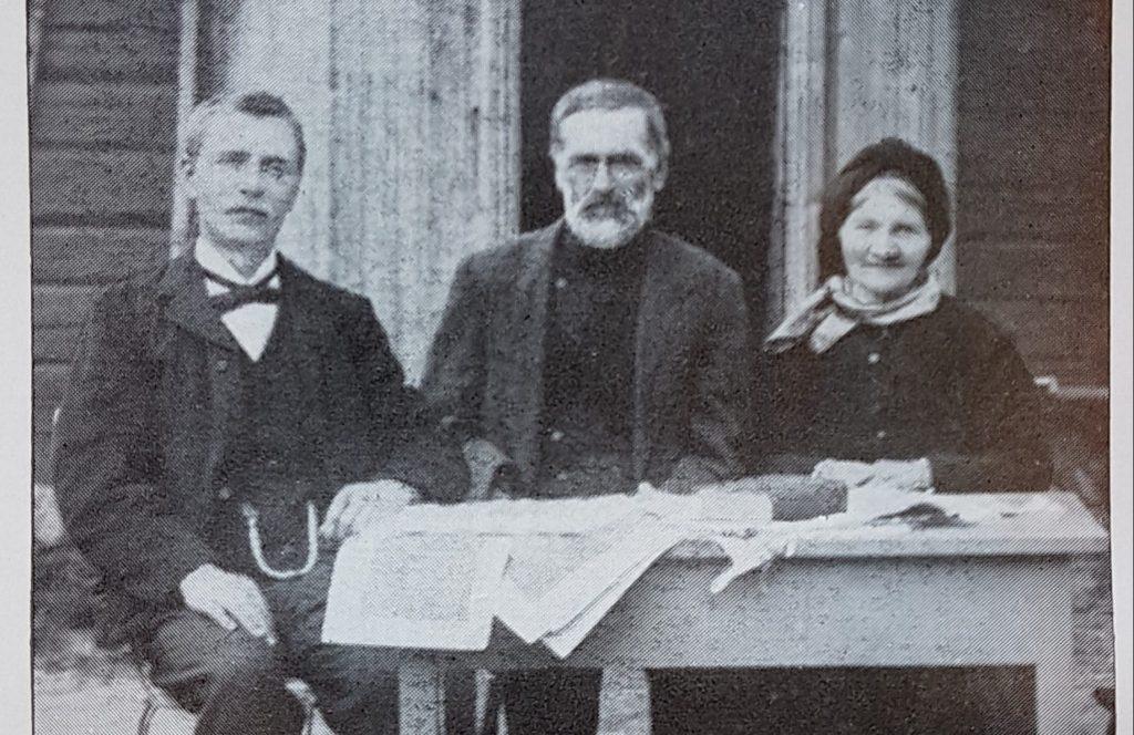 Ein yngre mann, og ein eldre mann og ei kvinne som sit ute ved eit bord med skrivne ark på. Alle er vendt mot kamera.